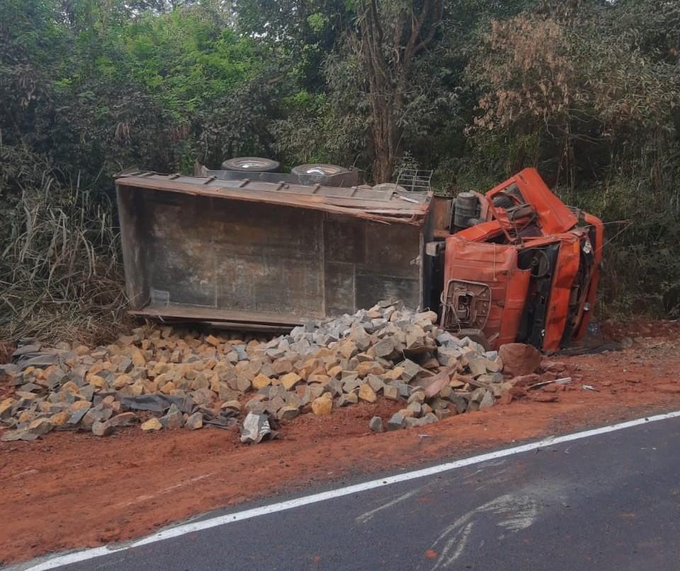 Caminhão carregado com pedras tomba e motorista fica gravemente ferido